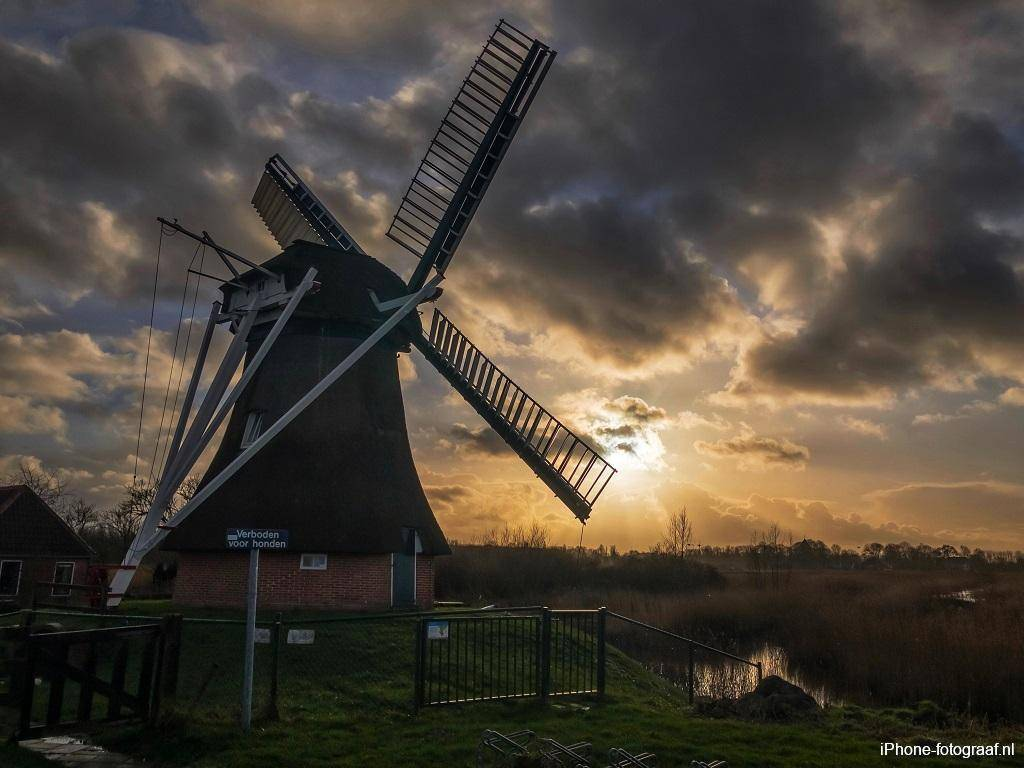 a windmill with a low sun