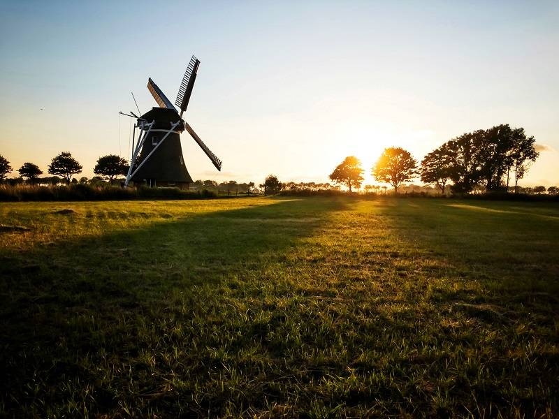 Photograph landscapes with your iPhone during the golden hour. On this photo you can see a mill and its long shadows. Sunset.
